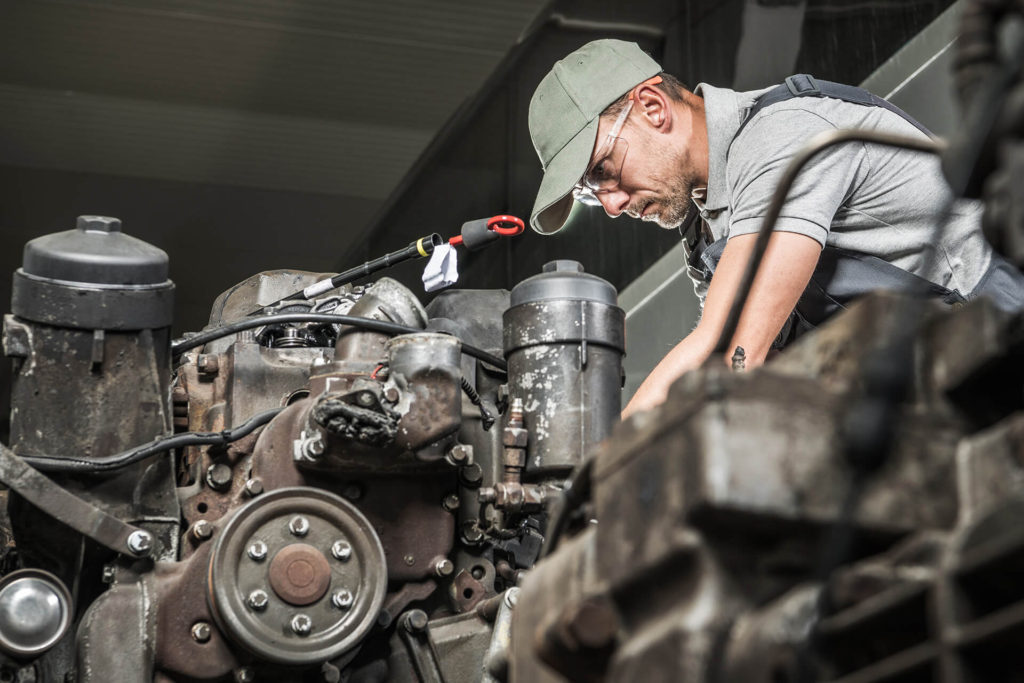 man working on engine with safety glasses